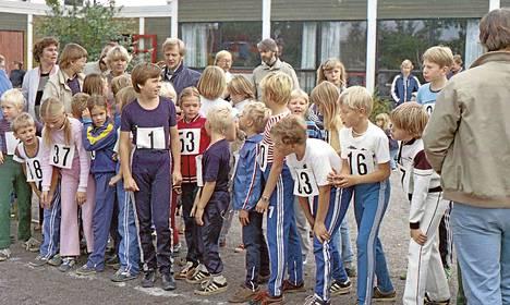 Lapset ovat lähtövalmiina juoksemaan. Meneillään on Kannelkylän kesäkisat 1970–80-luvun vaihteessa.