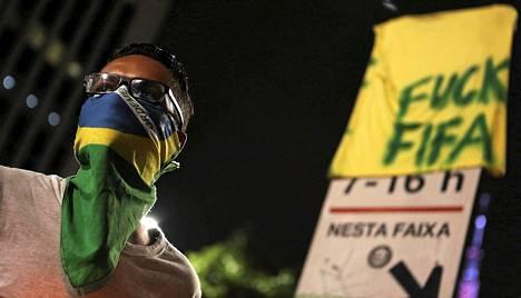 Jalkapallon MM-kisoja vastustava mielenosoittaja oli naamioitunut Brasilian lipulla koristetulla huivilla Sao Paulossa maaliskuun lopulla.