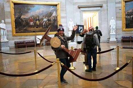 Mies kantoi Yhdysvaltain kongressin alahuoneen puhemiehen puhujakoroketta Washingtonissa ja vilkutti kameralle mielenosoittajien tunkeuduttua kongressirakennukseen.