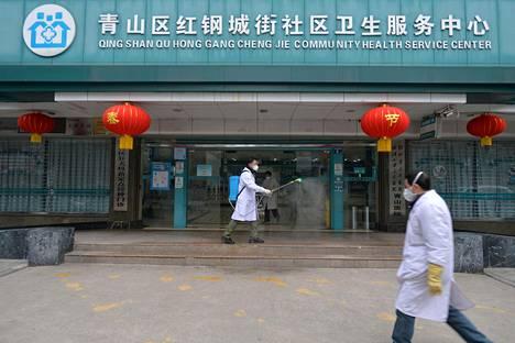 Lääkäri desinfioi terveysaseman sisäänkäyntiä Wuhanissa Kiinassa helmikuun alussa.