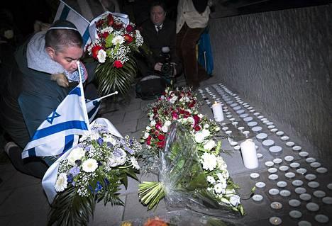 Ihmiset jättivät Tanskan lähetystön eteen kukkia Belgian Brysselissä maanantaina. Synagogan iskussa kuollut Dan Uzan haudataan keskiviikkona.
