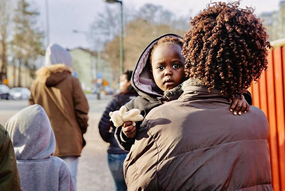 Äiti Achol Thon Duot kantaa 2-vuotiasta tytärtään Alek Khot Bioweita sylissään Tukholmassa.