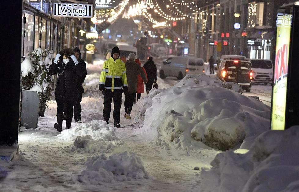 Jalankulkijoita ja lumikasoja Aleksanterinkadulla Helsingissä keskiviikkoaamuna.
