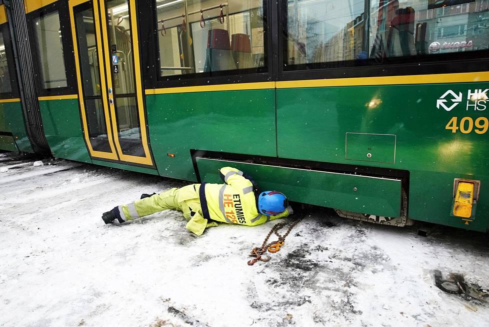 Etumies Kari Kiiski HKL:n raivausyksiköstä testaa vaunun kiskoille vetoa Töölön hallin pihassa.