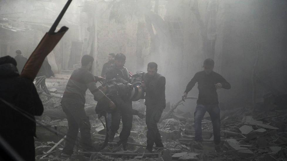 Members of the Syrian civil defence evacuate an injured civilian from an area hit by a reported regime air strike in the rebel-held town of Saqba, in the besieged Eastern Ghouta region on the outskirts of the capital Damascus, on February 20, 2018.