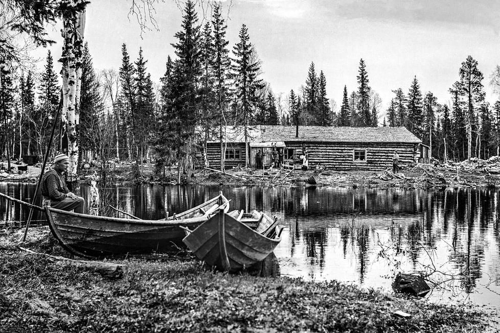 Ukkoherra Einari Ansala istuu veneessä Rovaniemen maalaiskunnan Ropsajoella. Vuonna 1941 rakennetun savottakämpän pääpirtti toimi myös purouiton tukikohtana. Vuonna 1947 kämpälle kuljetettiin hevosella elintarvikkeita niin sanottuna Amerikan apuna. Kuormassa oli jäädytettyä puhvelinlihaa jopa 100 kilon kimpaleina.