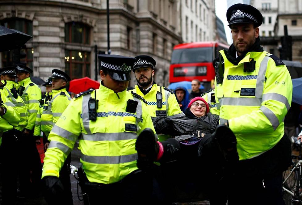 Poliisit ottivat mielenosoittajan kiinni tiesululla mielenosoituksen yhteydessä Lontoossa 14. lokakuuta.