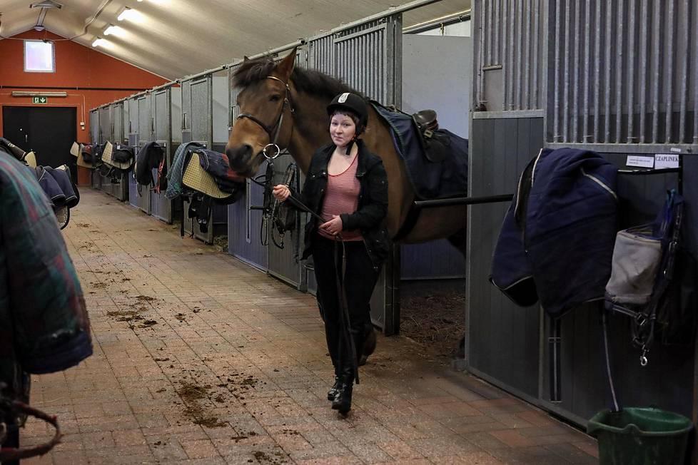 Koronaepidemian johdosta Peikin ratsastustallilla hevosten satulahuone on suljettu ja varusteet on siirretty jokaisen hevosen karsinan eteen. Anniina Häkkinen vei Einon lenkille.