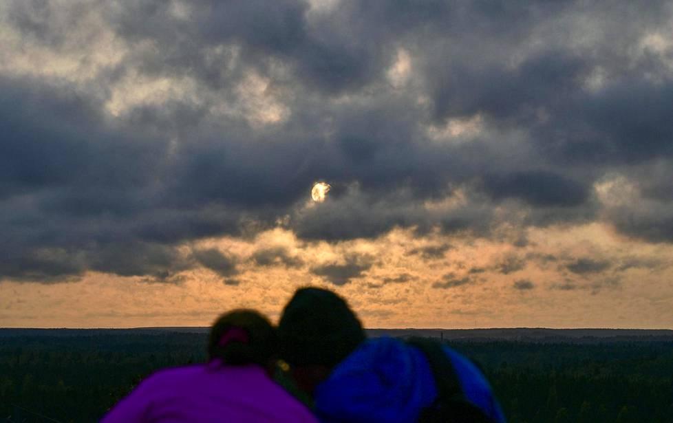 Ihmisiä ihailemassa auringonlaskua Malminkartanon täyttömäellä Helsingissä maanantai-iltana. Pilvet peittivät taivaan auringon laskiessa, ja kuva on otettu ennen auringonlaskuhetkeä.