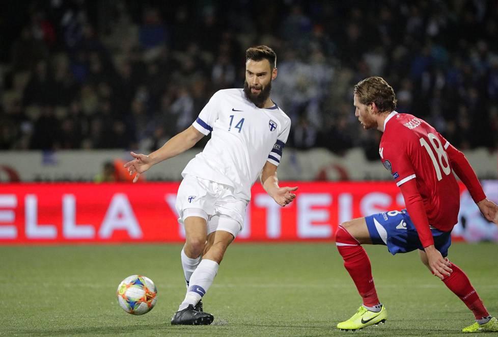 Liechtensteinin Nicolas Hasler yritti pysäyttää Huuhkajien kapteenin Tim Sparvin.
