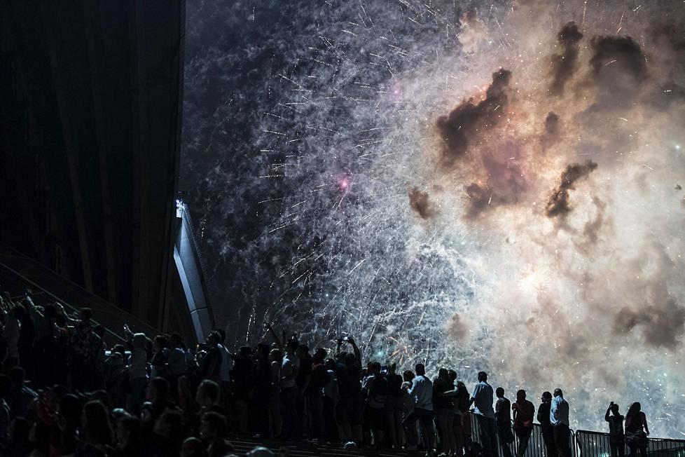 Ihmisjoukko seurasi ilotulitusta uutenavuotena Sydneyn oopperatalon lähellä Australiassa.