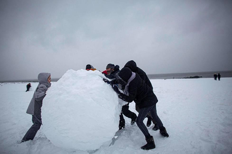 Ihmiset tekevät jättimäistä lumipalloa Brighton Beachissa.