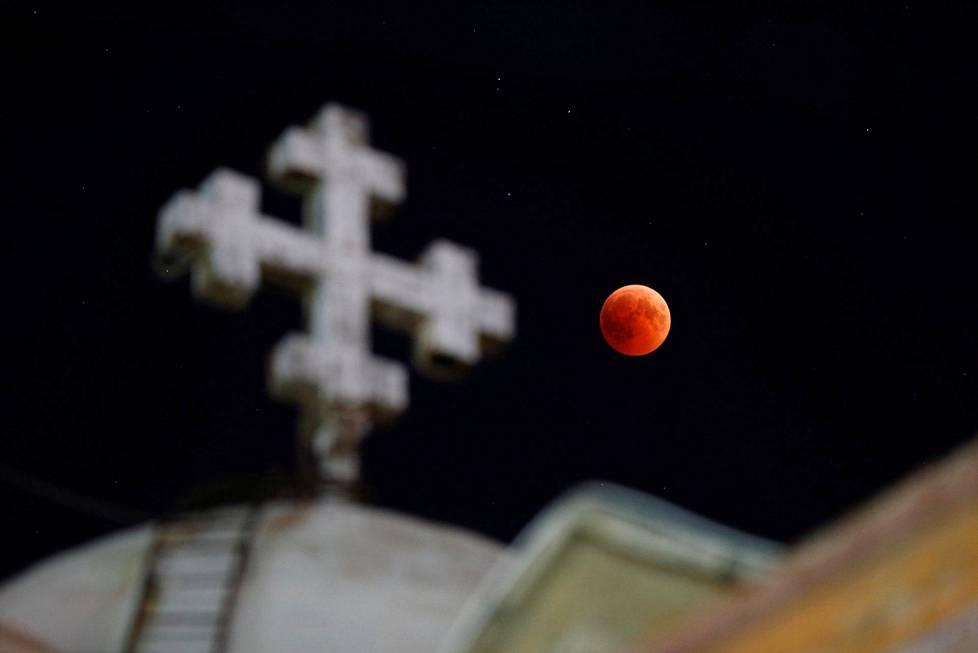 Punainen kuu näkyi koptilaiskirkon takaa Jordanian Ammanissa.