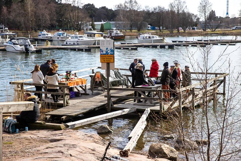 Joukko juhlijoita nautti vappueväistä ja auringosta Taivallahden mattolaiturilla Töölössä.