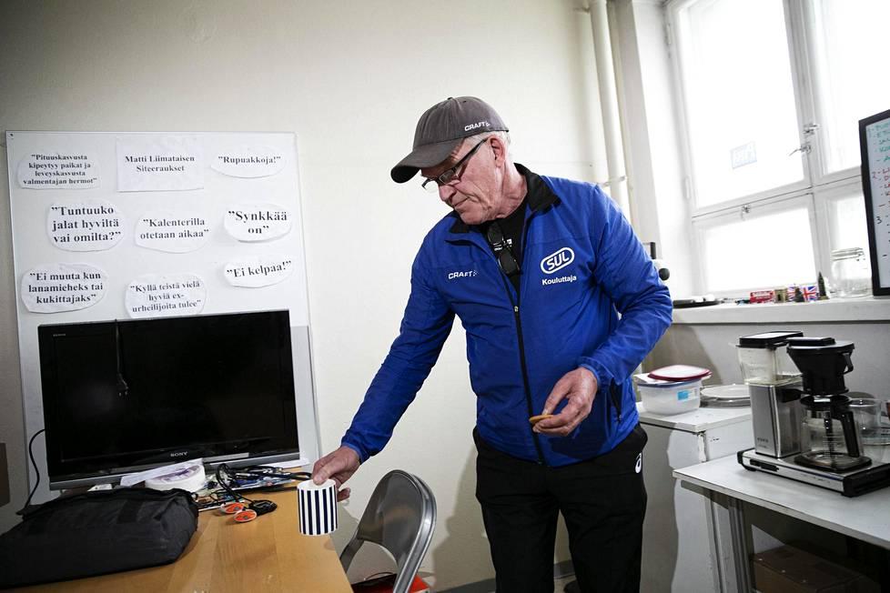 Matti Liimatainen valmentajakopissaan Pirkka-hallissa. Seinälle on kiinnitetty hänen tunnettuja siteerauksiaan.