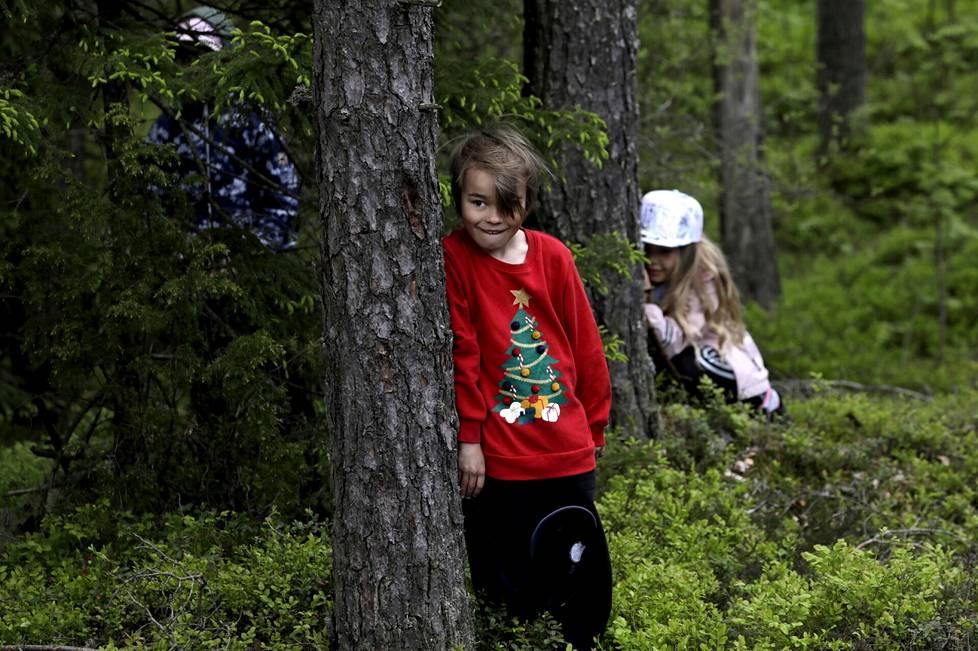 Metsäpiilo on kaikkien suosikkileikki. Vertti Ketonen (vas.) ja Mila Sipponen piilossa.