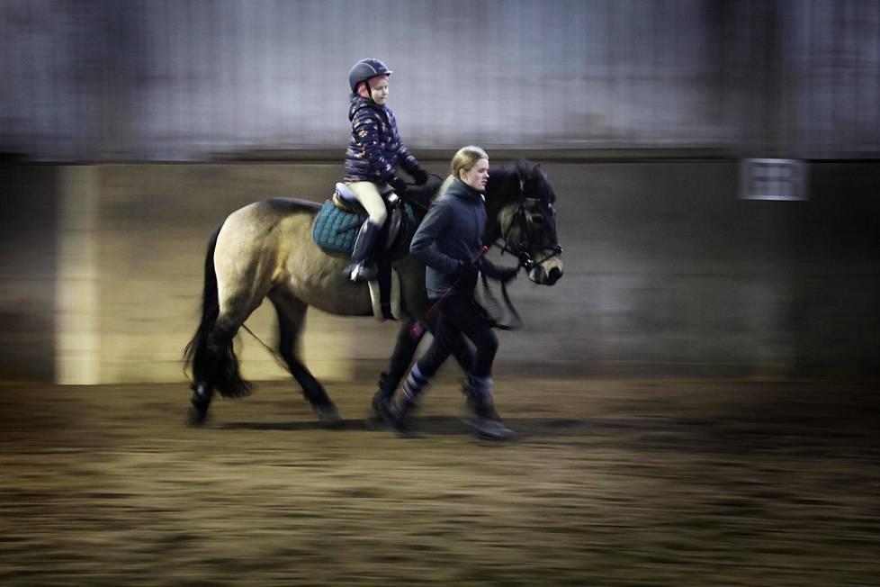 Léonie Rönnholm ratsastaa Rölli-ponilla. Vieressä avustaa Laura Koponen.