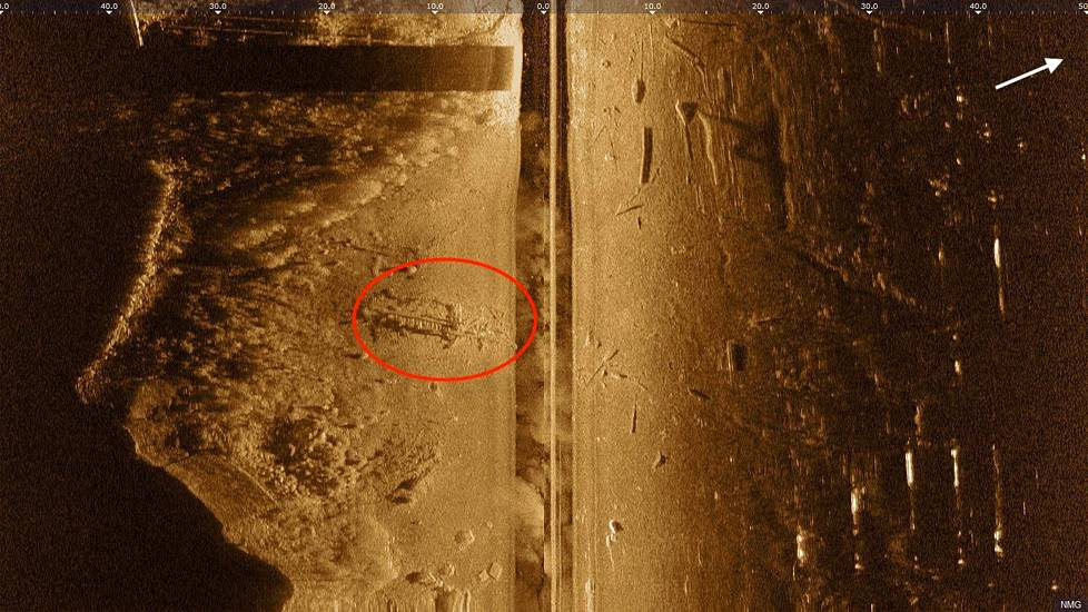 Hylky on ympyröity punaisella viistokaikuluotainkuvassa. Kuvassa vasemmalla aallonmurtajan seinämä. Hylyn massiiviset kaaret erottuvat rivistönä. Vasemmassa alakulmassa näkyy veneenlaskupaikan betonilaatta. Pohjalla on myös autonrenkaita, laituripainoja sekä irtonaista puutavaraa.