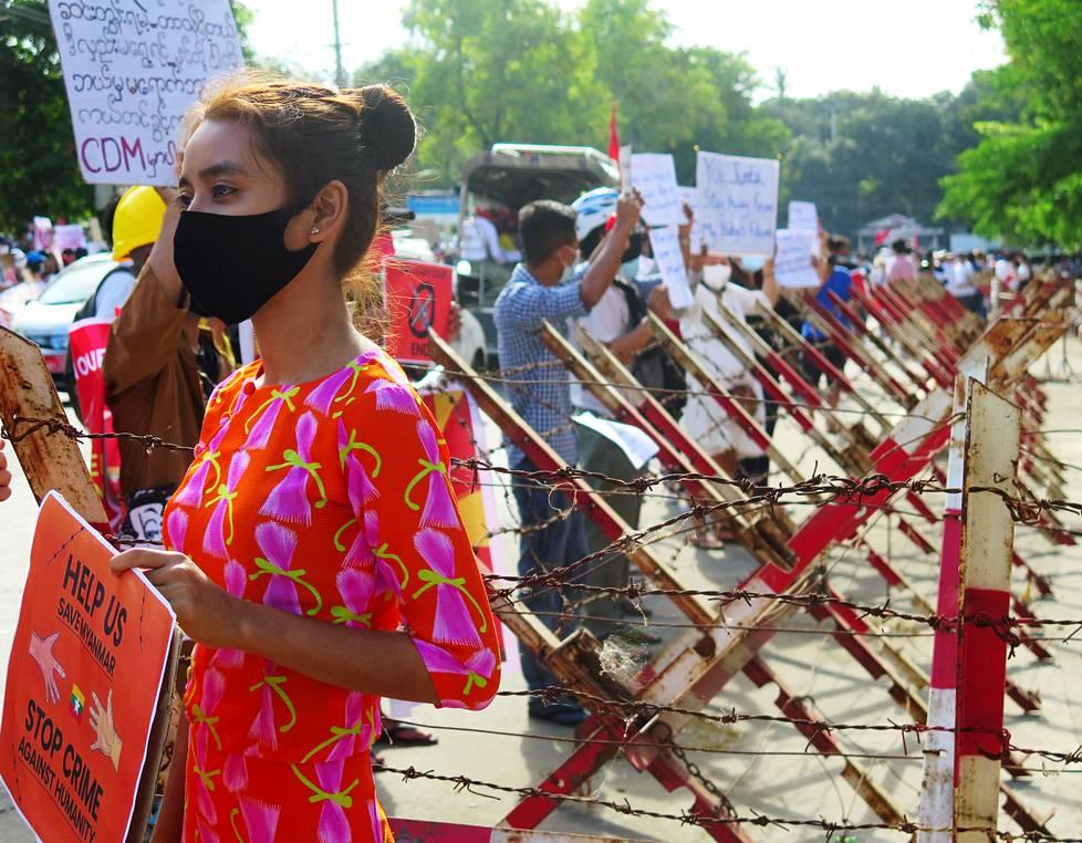 Nainen osoitti mieltään Kiinan lähetystön edessä Yangonissa.