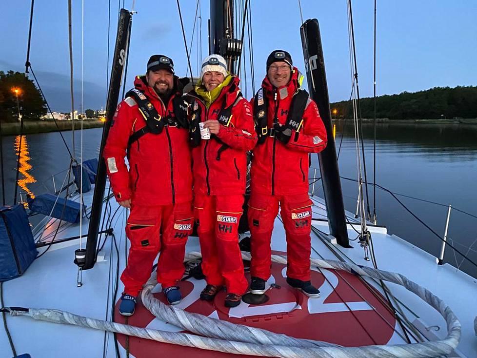 Jukka Jaskari, Marianna Puupera ja kippari itse Ari Huuselan Imoca 60 -luokan veneen kannella.