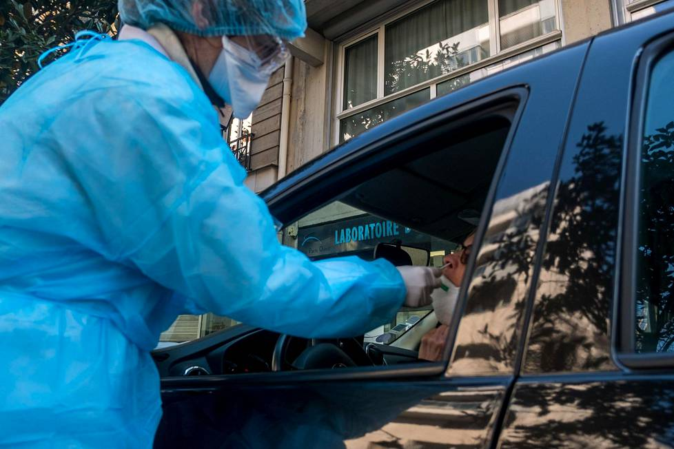 Pariisissa terveydenhoitohenkilöstö voi testauttaa itsensä koronavirustartunnalta erityisessä testipisteessä omassa autossa istuen. Näyte otetaan pumpulipuikolla nenästä.