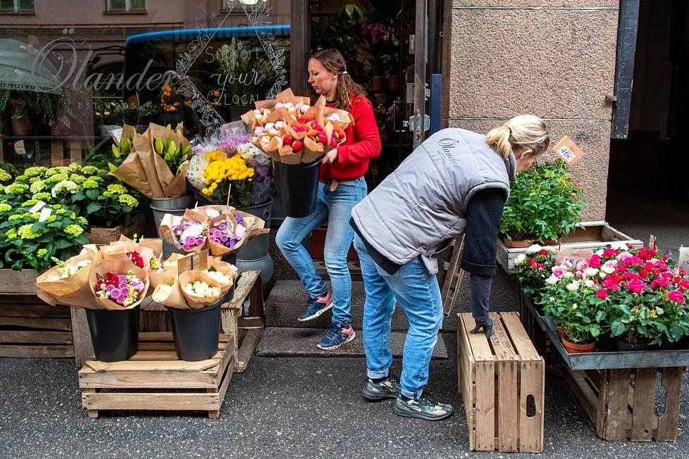 Kukkakauppias Charlotta Widén punaisessa puserossa asetteli perjantaiaamuna tarjontaansa esille Korkeavuorenkadulla yhdessä Hanna Huttusen kanssa