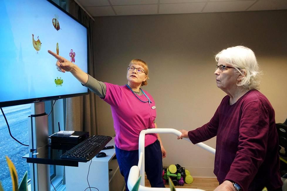 Tuula Katajainen pelaa tasapainoilupeliä, jossa pitää yhdistää astumalla oikeaan paikkaan yhdistää pyydetyt kuvat toisiinsa. Vierellä fysioterapeutti Katja Räsänen neuvoo.