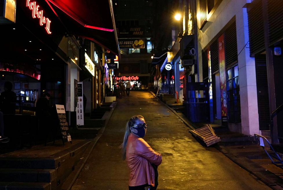 Nainen seisoi perjantaina tyhjien pubien edustalla Lan Kwai Fongin baarikortteleissa Hongkongissa.