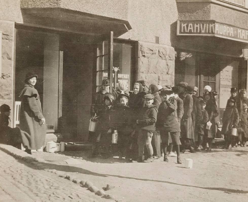 Ihmiset jonottivat maitokauppaan Helsingissä.