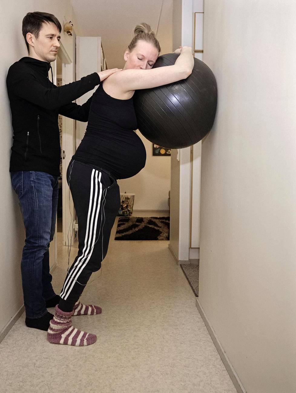 Hieronta, jumppapallo, taskussa TNS-laite – kipututkija Riikka  Holopainen ja lääkäri Markku Strandman lievittävät supistuk sista aiheutuvia kipuja kotona  monin tavoin. Kasvot on pidet tävä rentoina.