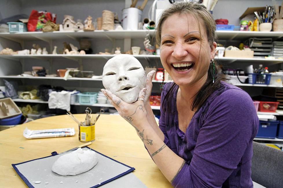Minna Lindh ei näe enää maalata tauluja, mutta huovuttaa ja muovailee, koska näkökyky on nyt sormissa. Työn alla on kevytmassasta päitä, jotka hän maalaa ja kiinnittää niille sitten hiukset ja silmäripset.