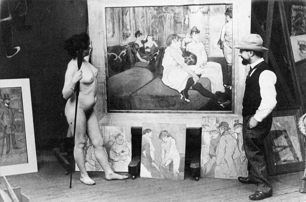 Henri de Toulouse-Lautrec (1864–1901) ja malli taiteilijan ateljeessa vuonna 1894. Esillä kuvia La Fleur blanchen ilotalosta.