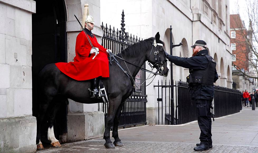 Poliisi tervehti vartijaa ja hevosta Westminsterin palatsin lähellä Lontoossa uudenvuoden aattona Lontoossa.