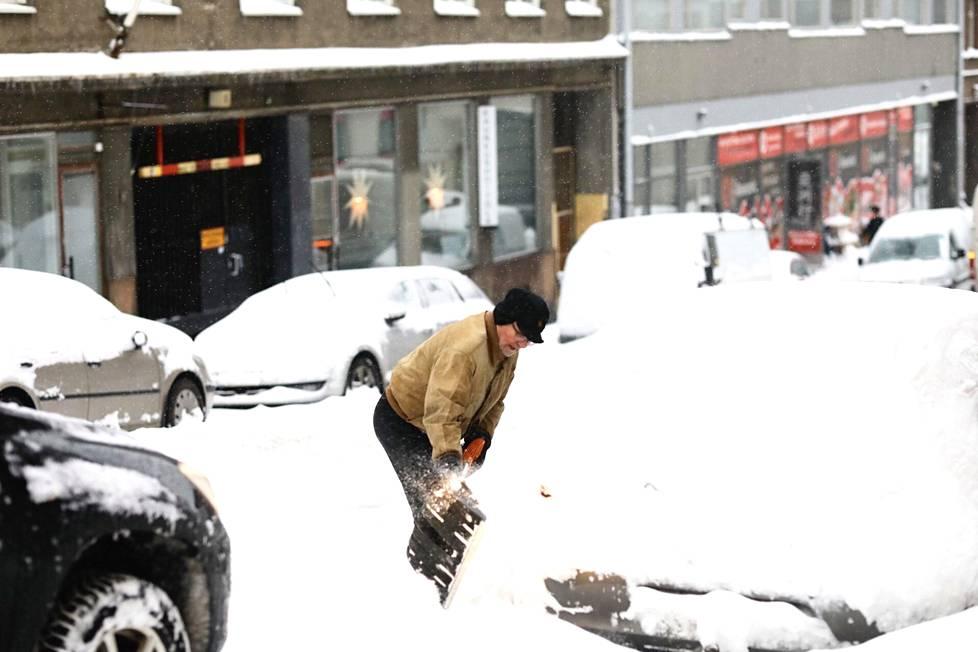 Martti Raulus puhdisti autoaan lumesta.