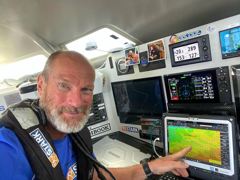 Ari Huusela tutki veneensä reititystä maanantaina. Huuselan sormi osoittaa Australian länsikärkeen Cape Leeuwiniin. Mitä tummempi väri ruudulla on, sen voimakkaammin tuulee. Vaaleanpunainen kuvake kartan vasemmassa reunassa on Huuselan vene.