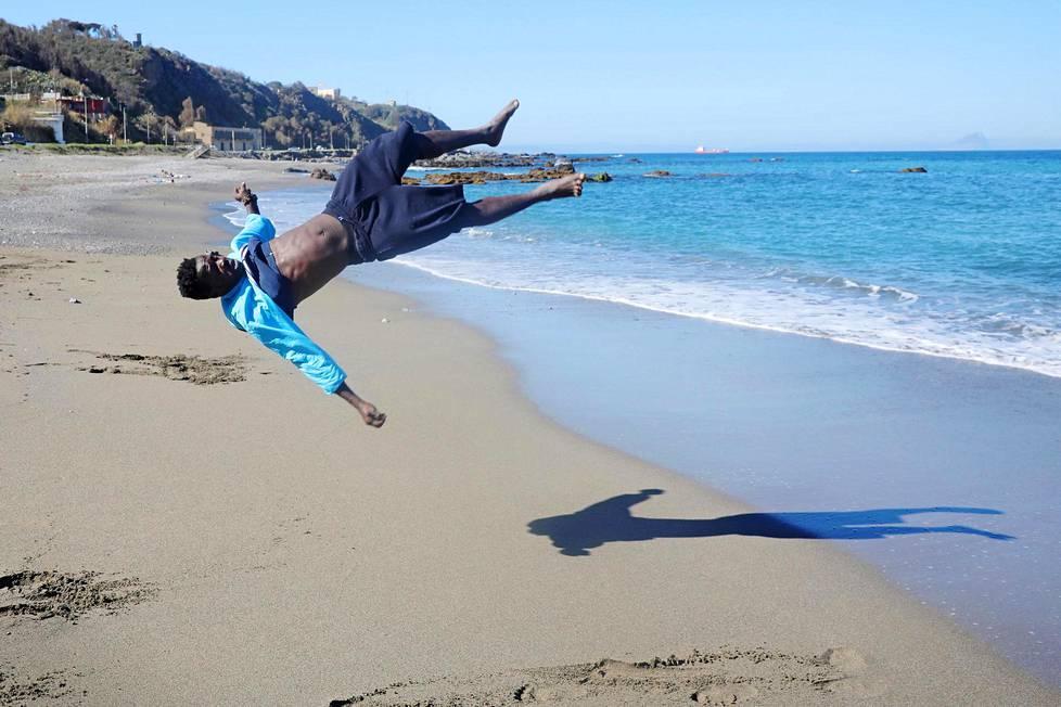 Kamerunilainen Christian Tchiemou Jr heittää voltin hiekkarannalla Espanjaan kuuluvassa Ceutassa, josta näkee Gibraltarinsalmen yli Eurooppaan.