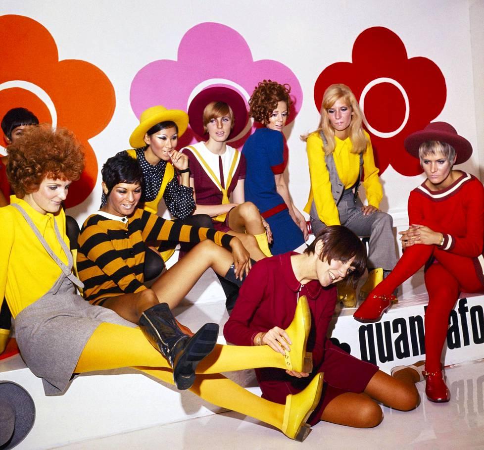 Mary Quant (edessä) malleineen esittelee uutta kenkämallistoa vuonna 1967. Taustalla näkyy Quantin kuuluisa logo eli viisiterälehtinen pelkistetty päivänkakkara.