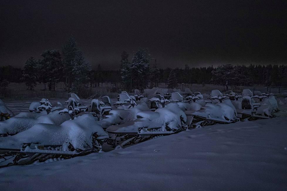 Lumen peittämiä moottorikelkkoja Napapiirillä.