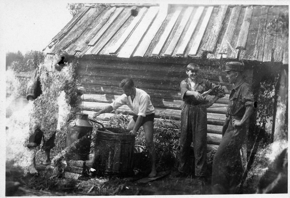 Eugen Wist pontikkapannun ääressä vuonna 1942. Hugo Sopanen ojentaa pulloa raittiina tunnetulle Muisto Lassilalle.