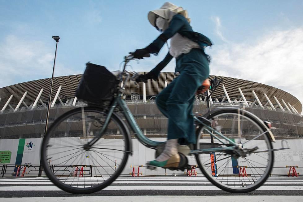 Pyöräilijä ajoi kasvosuojuksen kanssa Tokion uuden olympiastadionin rakennustyömaan ohitse. Arkkitehti Kengo Kuma palkattiin suunnittelemaan Zaha Hadidin suunnitelmaa halvempi toteutus.