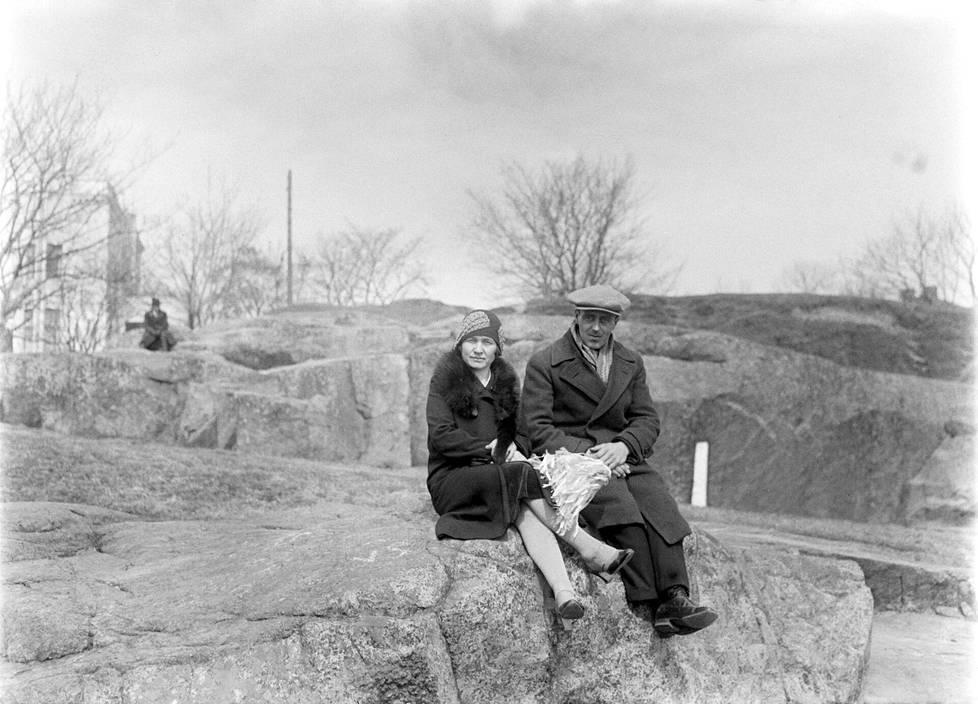 Mies ja nainen istuvat Kaivopuiston kallioilla vappuna 1920-luvulla. Naisella on kädessään vappuviuhka.