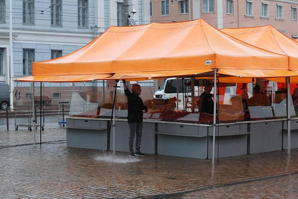 Torikauppiaat valmistautuivat päivään Helsingin kaupungintalon edustalla tiistaiaamuna.