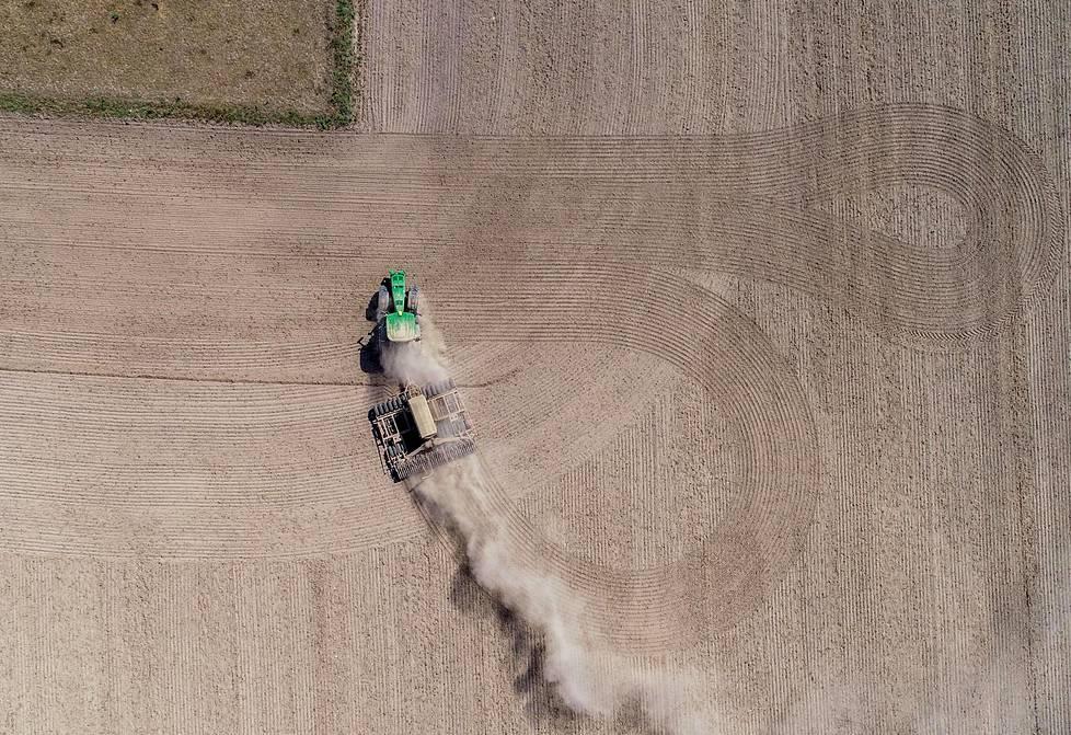 Saksalainen maanviljelijä kylvää rapsia peltoon Heinersdorfissa. Kylvö nostattaa kuivasta maasta paljon tomua ilmaan.