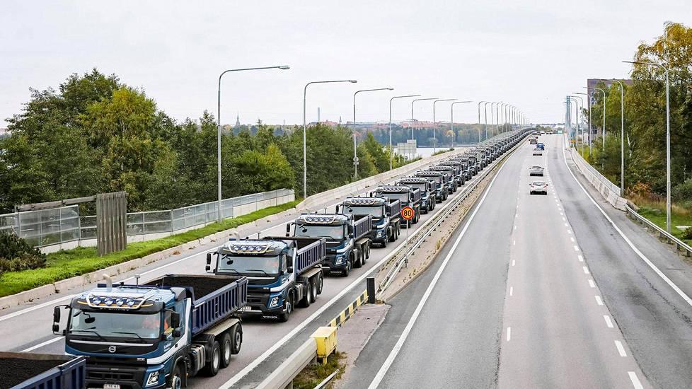 Tältä näyttäisi, jos kaikki Suomen tekonurmijalkapallokentille levitetyt kumirouheet vietäisiin kerralla. Laskelmien mukaan Suomen tekonurmikentille on levitetty 37 miljoonaa kiloa kumirouhetta. Sellaisen rouhemäärän tilavuus on 74 970 kuutiometriä. Yhden Volvo FMX -kuorma-auton lavalle mahtuu 13 kuutiometriä lastia. Koko rouhemäärän kuljettamiseen tarvittaisiin siis 5 767 kuorma-autoa. Jos kaikki nuo autot asettuisivat metrin välein peräkkäin Länsiväylälle, letka olisi noin 63 kilometriä pitkä ja ulottuisi Helsingin Ruoholahdesta Karjaan Rejböleen. (Kuvassa näkyvän kuljetusyhtiön autoissa ei oikeasti kuljeteta kumirouhetta.)
