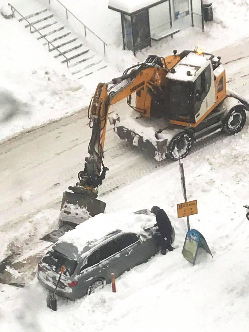 Sopivasti paikalle sattunut kaivinkone auttamassa autoilijaa, jonka auto oli lumen saartama.