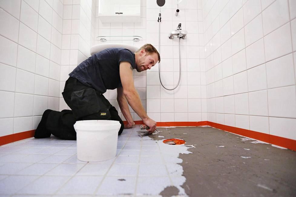 Yrittäjä Jani Vaittinen mikrosementöi kylpyhuonetta Helsingissä. Kuvassa hän levittää ohuen kerroksen mikrosementtiä lattialaatan päälle. Ennen sementöintiä hän tasoitti laatat grueso-pohjustusaineella. Koko urakka kestää noin kymmenen päivää.