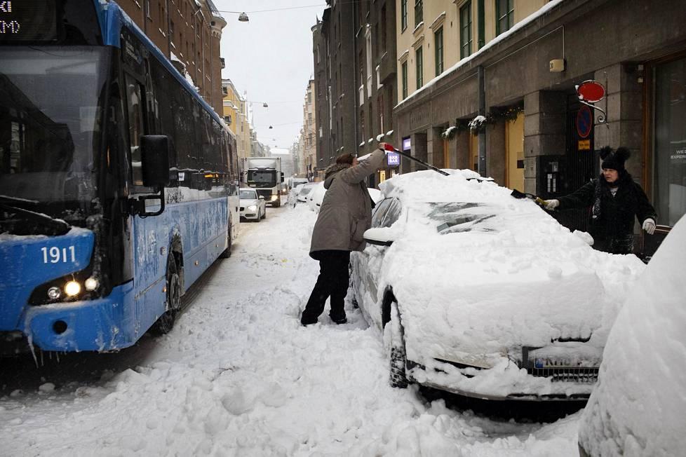 Eva Malm ja Annukka Hänninen kaivoivat autoa lumesta Fredrikinkadulla.