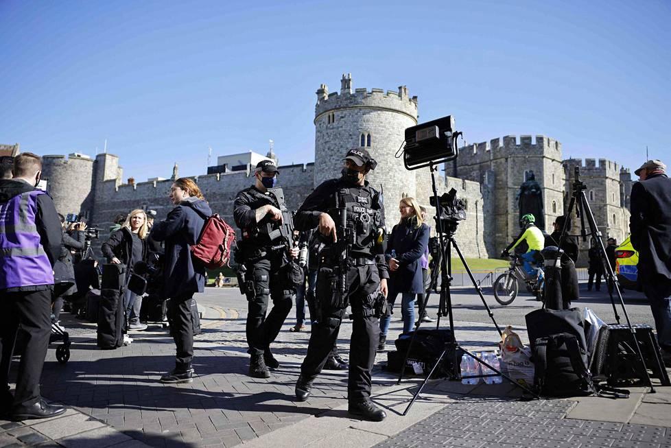 Poliisit kävelivät median edustajien keskuudessa Windsorin linnan alueella. Prinssi Philipin hautajaisissa oli mittavat turva- ja koronatoimet.