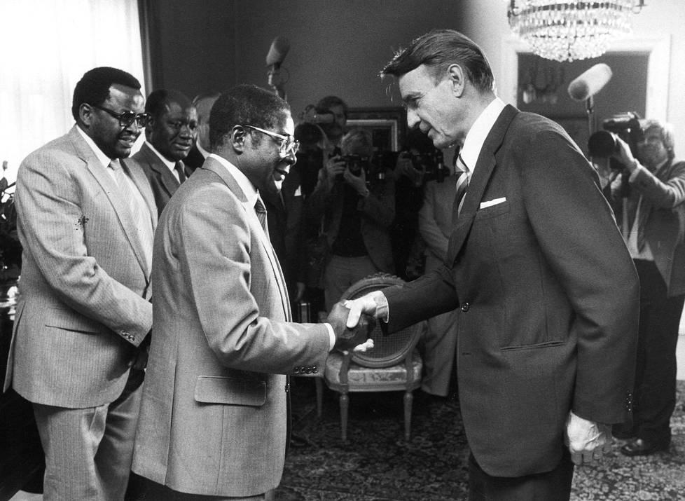 Zimbabwen tuore pääministeri Robert Mugabe tapasi Helsingissä presidentin sijaisen, pääministeri Mauno Koiviston. Koiviston koura on tunnetusti iso, mutta Mugaben koura ei näytä erityisen pieneltä Koiviston puristuksessa.