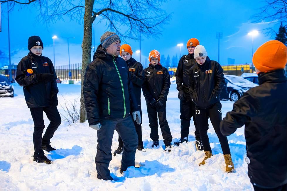 Valmentaja Tomi Vuorenmäki antoi ohjeita Esport Oilersin 13-vuotiaiden salibandyjoukkueen pelaajille Tapiolan urheilupuistossa kinoksien keskellä.